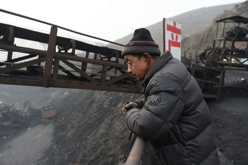 A worker watches over activities near a coal mine in China's northern Shanxi province on Nov 20.