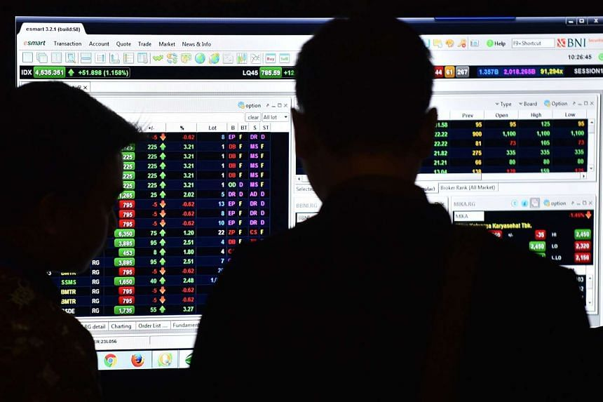 Men looking at a screen during a stocks expo at the Indonesia Stock Exchange in Jakarta.