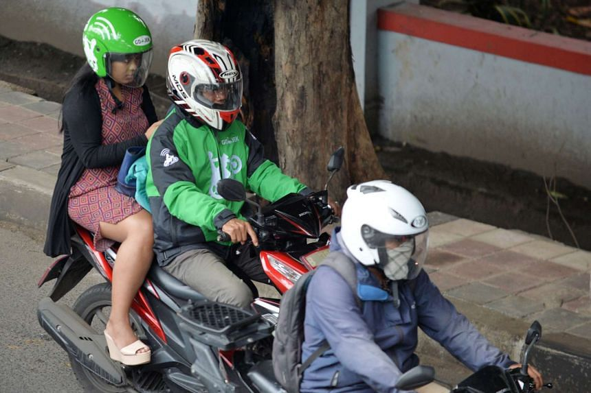 A motorcycle taxi (centre) transporting a customer in Jakarta on Dec 18.
