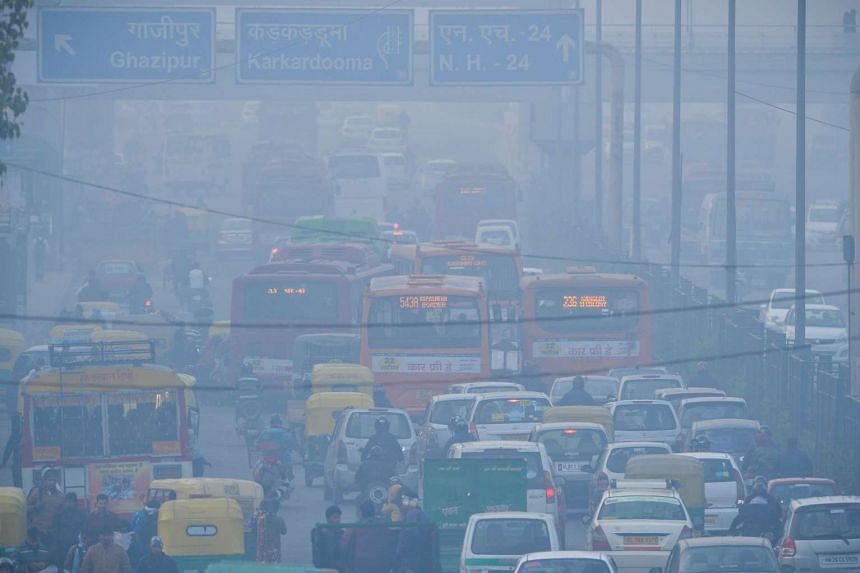 Indian commuters travel on a polluted road near a bus terminus in the Anand Vihar District of New Delhi.