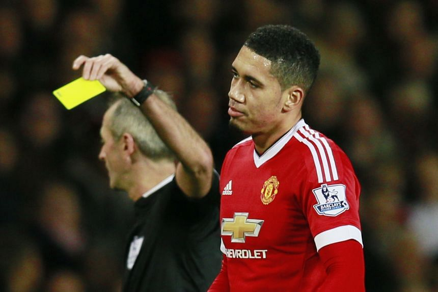 Referee Martin Atkinson (left) shows a yellow card to Manchester United's Chris Smalling on Dec 28, 2015.