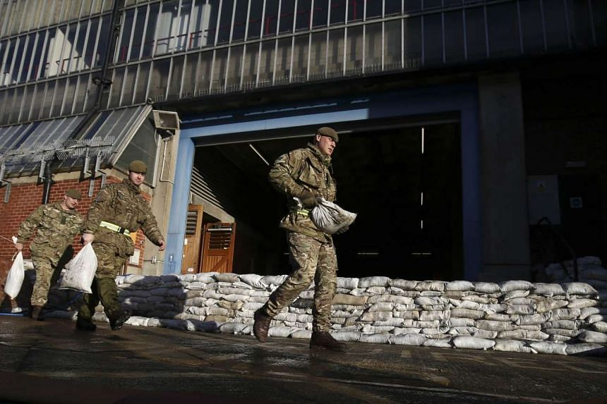 British soldiers carry sandbags as they make flood defences n the city of York, England, on Dec 29.