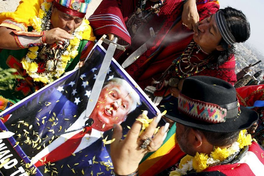 Peruvian shamans holding a poster of US Republican presidential candidate Donald Trump perform a ritual of predictions for the new year at Morro Solar hill in Chorrillos, Lima, Peru, on Dec 29, 2015.