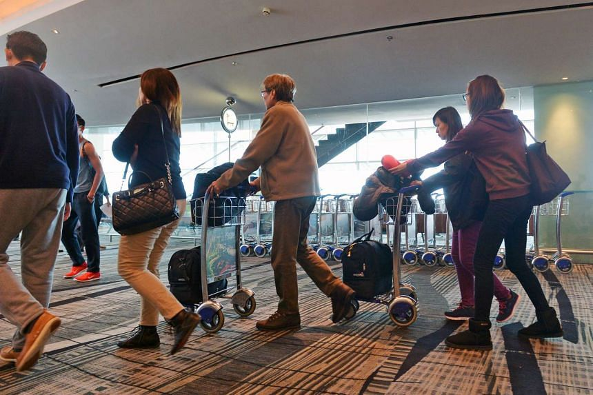 Passengers getting trolleys for their luggage.
