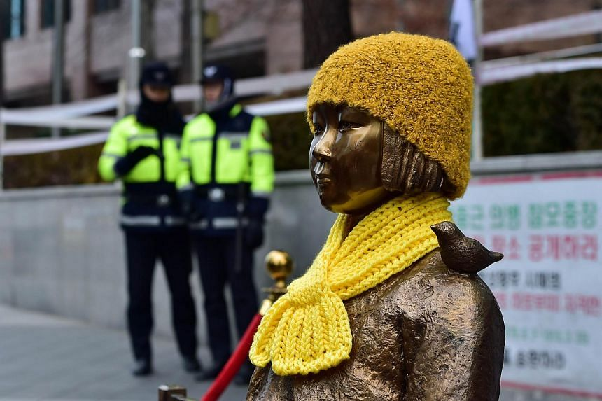 """South Korean policemen  stand guard near a statue of a teenage girl called the """"peace monument"""" for former comfort women."""