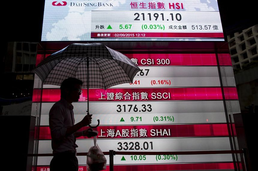 A man walks past a panel displaying figures of China stock indexes and Hang Seng Index in Hong Kong.