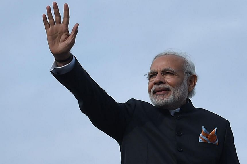 Indian Prime Minister Narendra Modi waves as he boards an aeroplane at the Kabul International Airport.