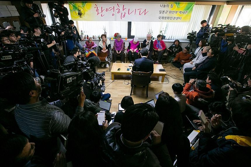 South Korean Second Vice-Foreign Minister Cho Tae Yul (sitting with back to camera) meeting former comfort women at a shelter in Seoul yesterday.