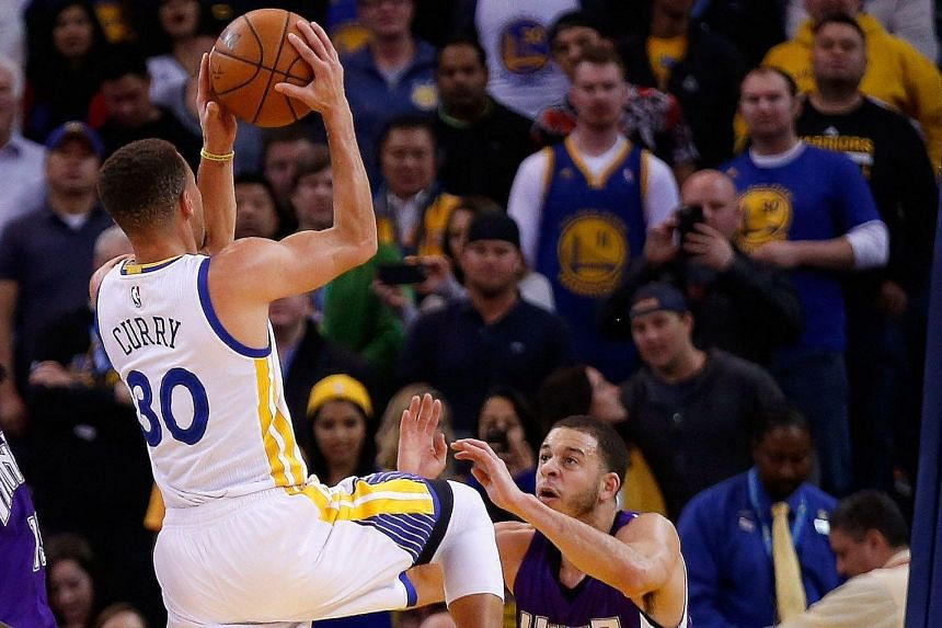 Stephen Curry (left) shooting over his younger brother Seth of the Sacramento Kings during the Golden State Warriors' 122-103 win at Oracle Arena on Monday.
