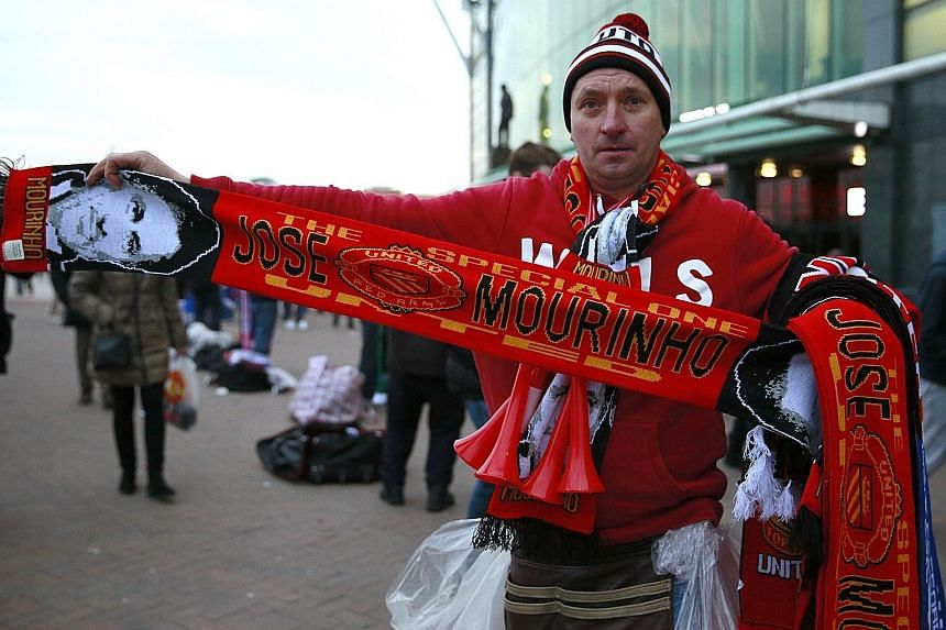 A street seller with a Manchester United scarf that has Jose Mourinho's face woven onto it. The scarves were being sold outside Old Trafford prior to the United-Chelsea clash.