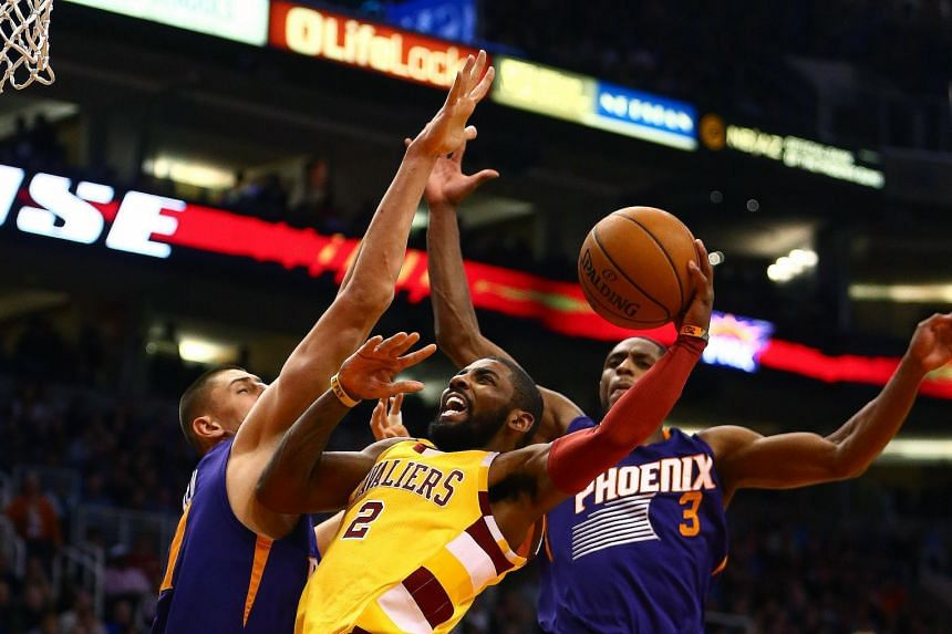 Cleveland Cavaliers guard Kyrie Irving (centre) driving to the basket against Phoenix Suns guard Brandon Knight (right) and centre Alex Len. The Cavs won 101-97 to avoid their season's first three-game losing streak.