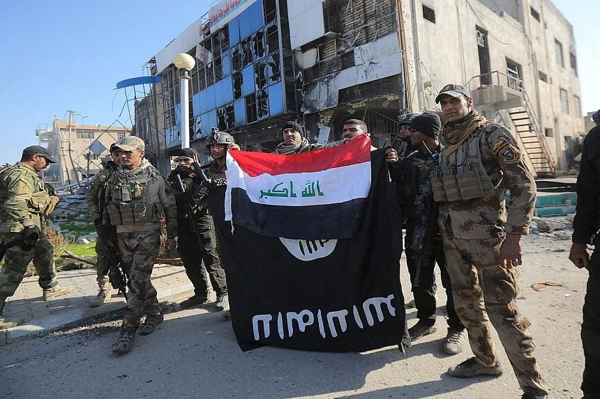 Members of Iraq's security forces (right) holding an Iraqi flag with an ISIS flag, which they had pulled down at a Ramadi government complex, while counterterrorism forces (below, right) celebrate on Monday after the city was retaken from ISIS. The a