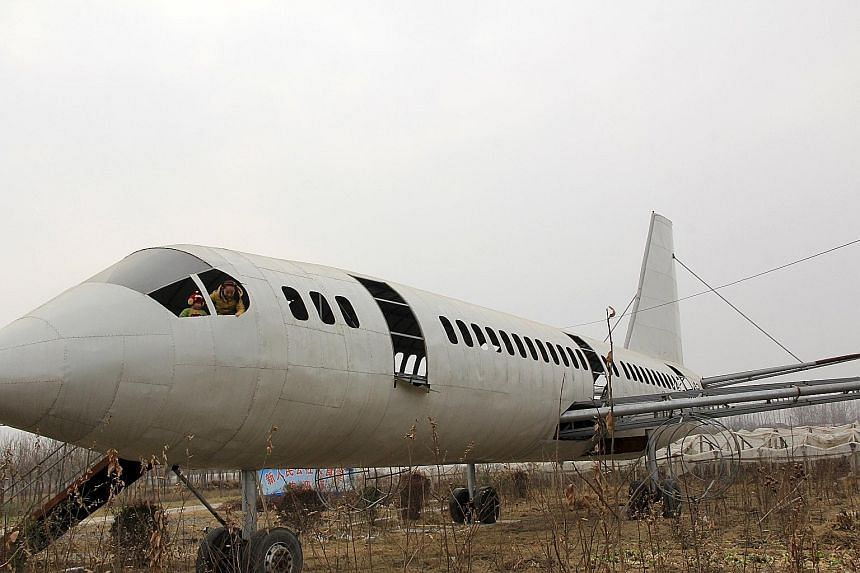 """Children playing in a """"homemade"""" Boeing 737 replica in a crop field in Neihuang county, China's Henan province, on Sunday. Farmer Wang Lanqun spent a year making the 35m-long installation, and there are plans to transform it into a restaurant, accord"""