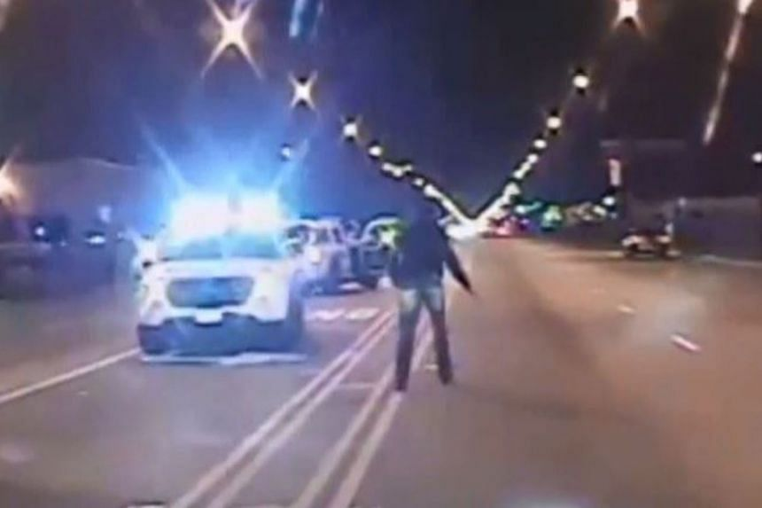 In a screen grab, Laquan McDonald (right) walks past police cars carrying a knife, before being shot.