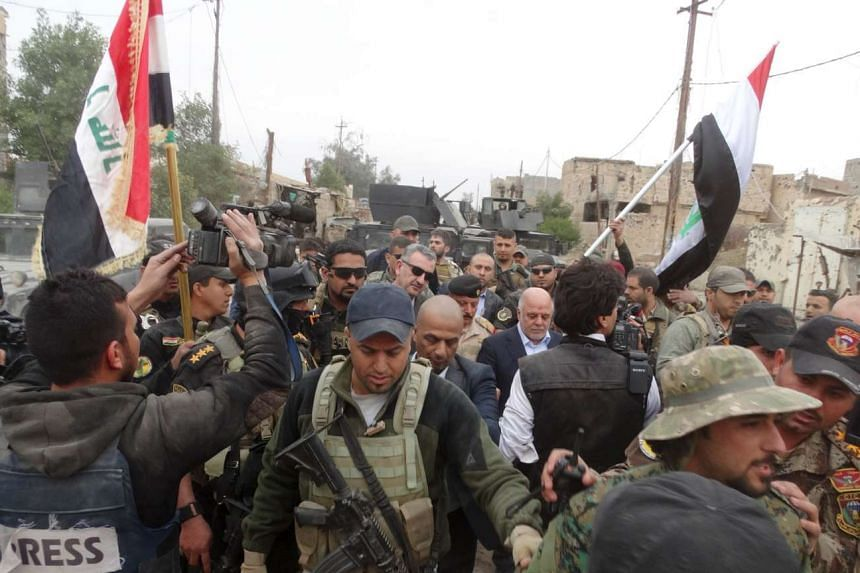 Iraqi Prime Minister Haider al-Abadi (centre, right) walks with his security detail in the city of Ramadi.