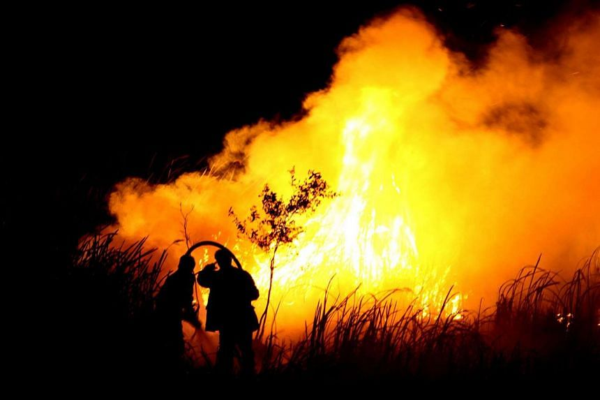 Indonesian men put out a fire in Ogan Ilir, southern Sumatra on Oct 22, 2015.