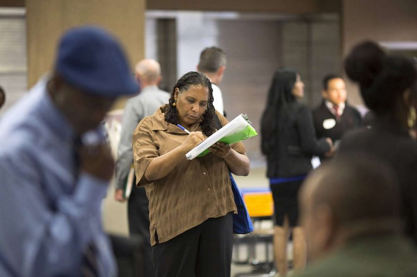 A woman filling up an application at a job fair in Los Angeles, California.