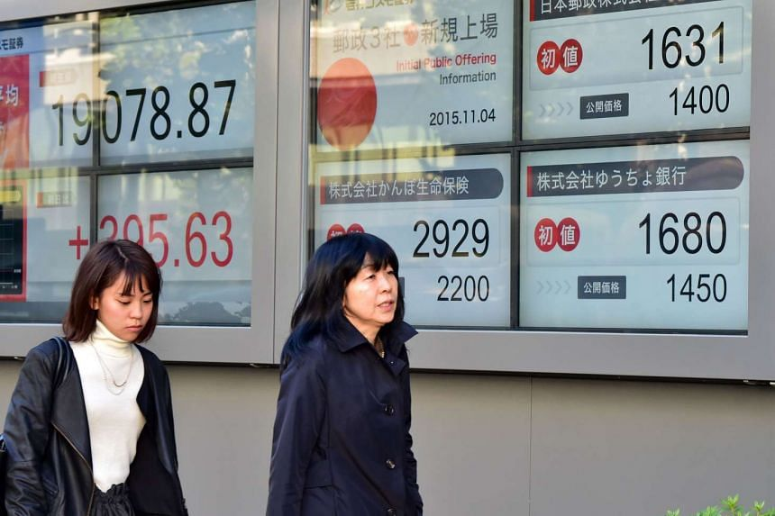 Pedestrians walk past a share prices board displaying prices of Japan Post Holdingsin Tokyo on Nov 4.