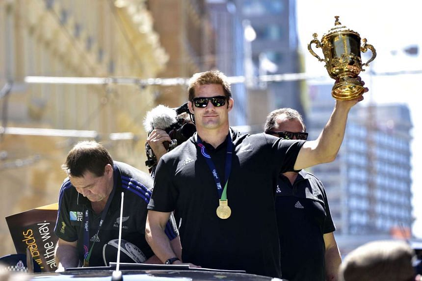 Richie McCaw holds the Webb Ellis Cup during a parade following their Rugby World Cup win.