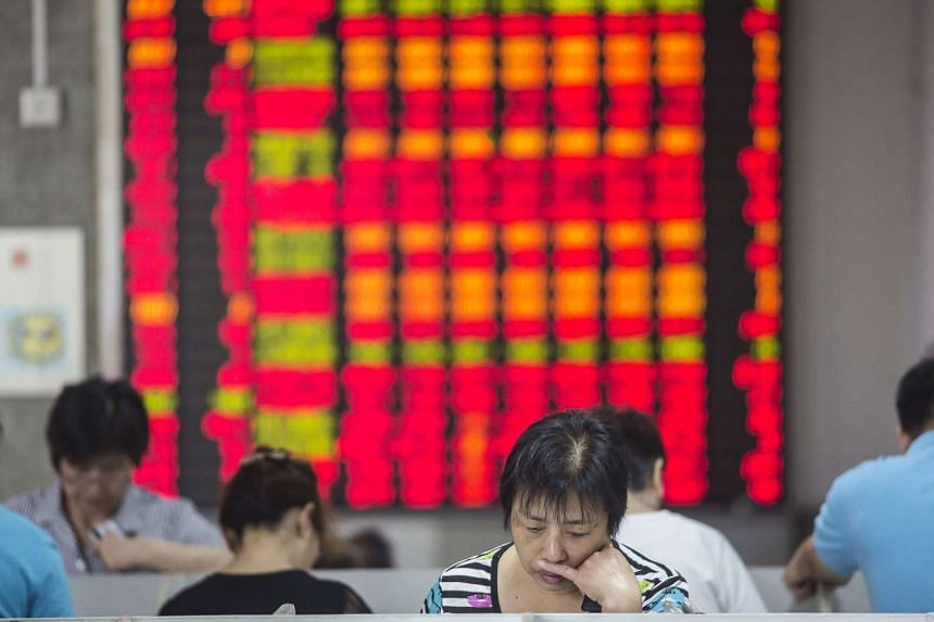 A woman stands in front of an electronic board displaying share prices at a securities exchange house in Shanghai, China.