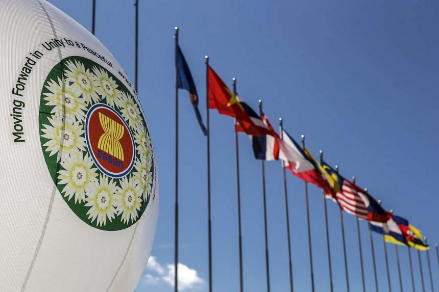 A balloon carries the Asean logo as it stands next to Asean members and dialogue partners flags.