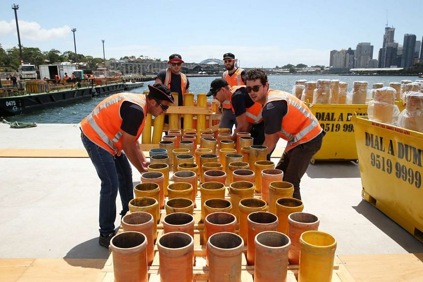 Workers loading racks of mortar tubes for the Sydney New Year's Eve display onto a barge in Sydney, Australia, on Thursday, Dec 24, 2015. Tens of thousands of people are expected to gather on the foreshores of Sydney harbor to watch a midnight firewo