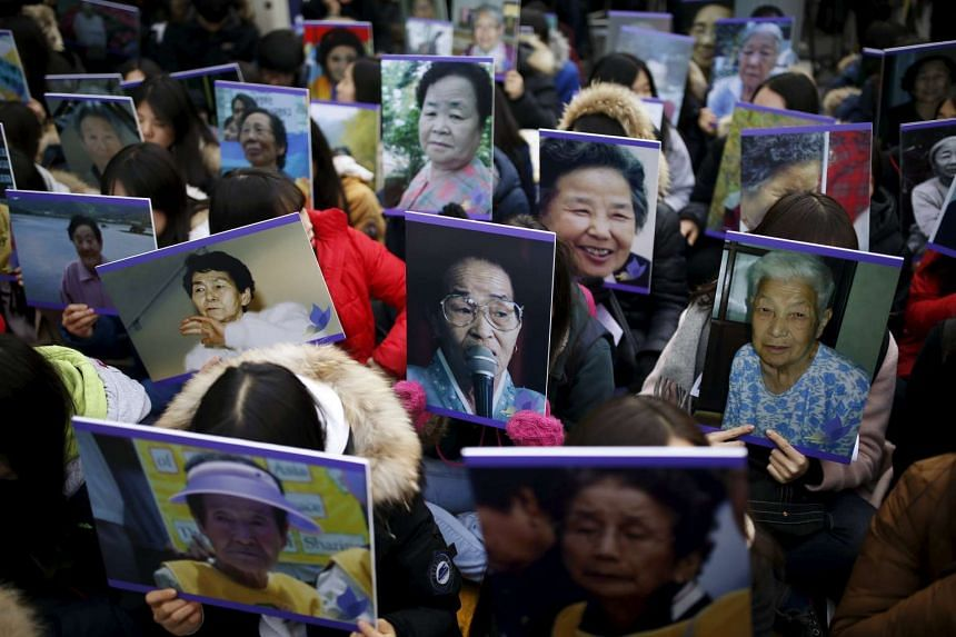 "Students hold portraits of deceased former South Korean ""comfort women"" during an anti-Japan rally in front of the Japanese embassy in Seoul on Dec 30, 2015."