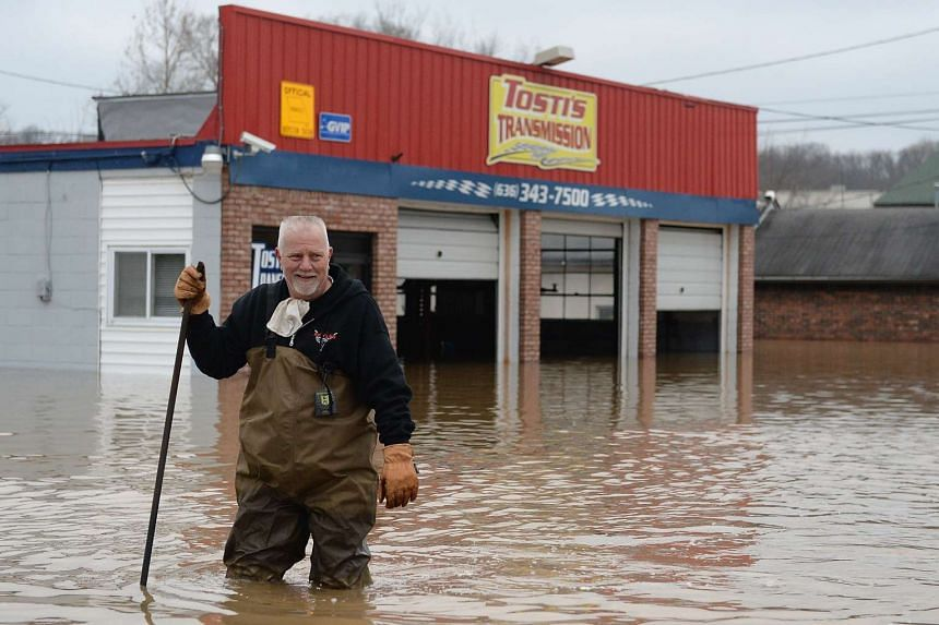 John Tosti, owner of Tosti's Transmission wades in the water after inspecting his business as it takes on floodwater on Dec 30 in Fenton, Missouri.