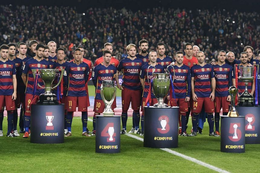 Barcelona's players pose with trophies before the match against Real Betis.