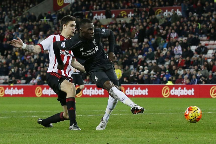 Christian Benteke (right) scores the first goal for Liverpool in their match against Sunderland.