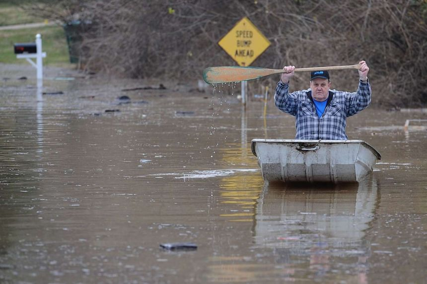 A resident canoes himself down a street submerged in floodwater from the Meremac River on Dec 30 in Arnold, Missouri.
