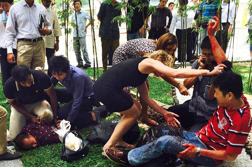 The man being pinned down by two others had allegedly attacked the man in red (right) with a knife on Nov 14 at Raffles Place.