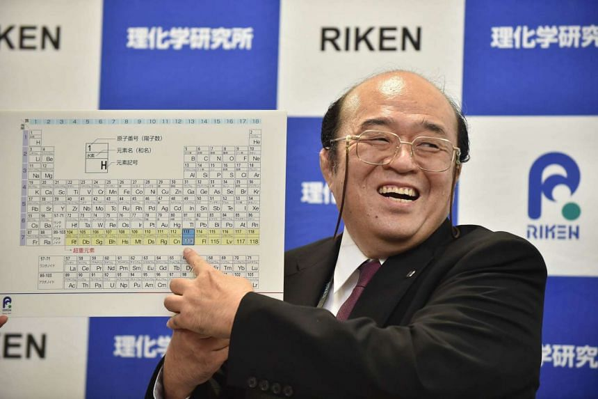 Kosuke Morita, the leader of the Riken team, smiles as he points to a board displaying the new atomic element 113.