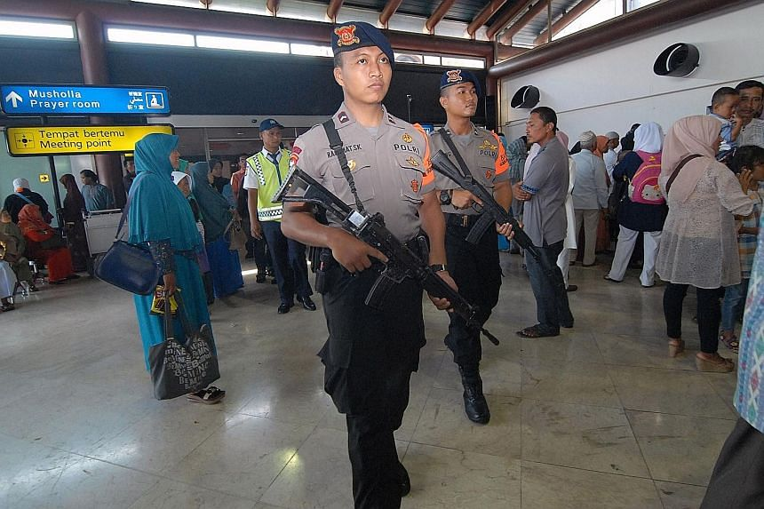 Indonesian police officers patrolling at Jakarta's Soekarno-Hatta airport yesterday. Officials say security has been ratcheted up for New Year's Eve this year in more than just the capital cities, following terrorist attacks in cities around the worl