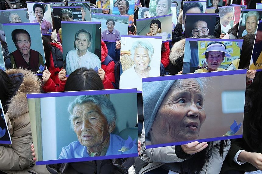 South Korean protesters with pictures of deceased former comfort women during a weekly anti-Japan rally in front of the Japanese Embassy in Seoul. The plight of South Korea's comfort women is a hugely emotional issue that has for decades marred ties