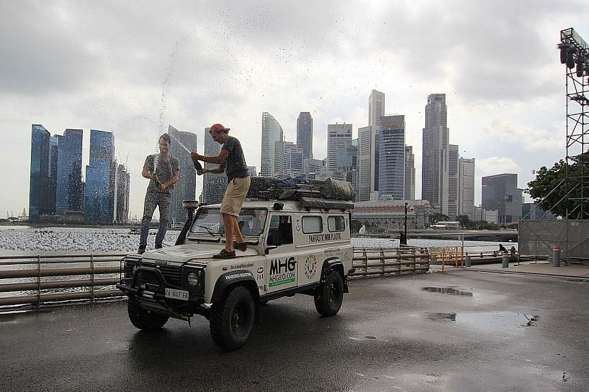Above: Mr Sabatini (left) and Mr Poccianti celebrate their arrival here by popping champagne atop their Land Rover with the Singapore skyline in the background. Above, left: On part of their road trip, Mr Poccianti (left) and Mr Sabatini had to be ac