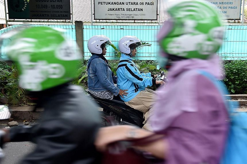 A female motorcycle taxi rider with her passenger in Jakarta. A flurry of new motorcycle taxi options in the metropolis have given Indonesia's growing middle class greater choice of transport. The new services are a challenge to traditional motorcycl