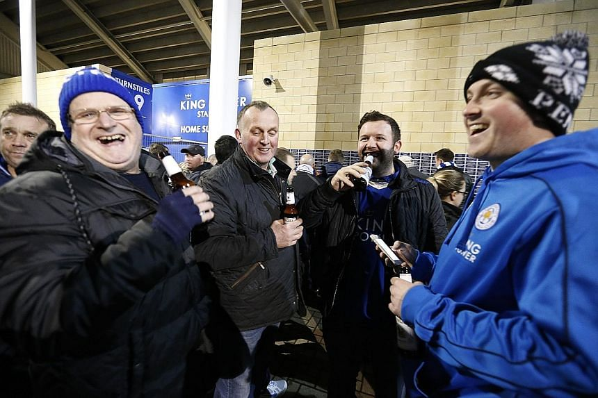 Leicester City fans with their free bottles of beer before the Man City match.