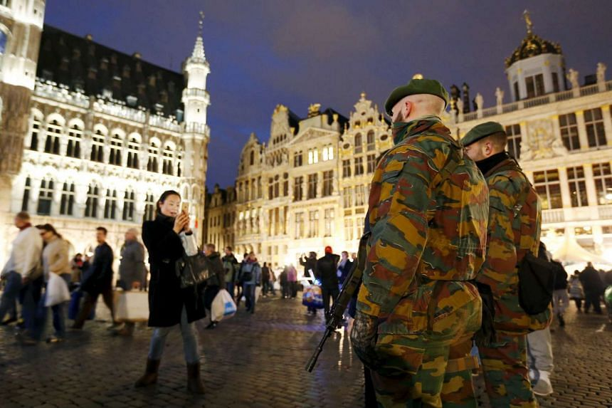 Belgian soldiers pose for a photograph as they patrol Brussels' Grand Place.