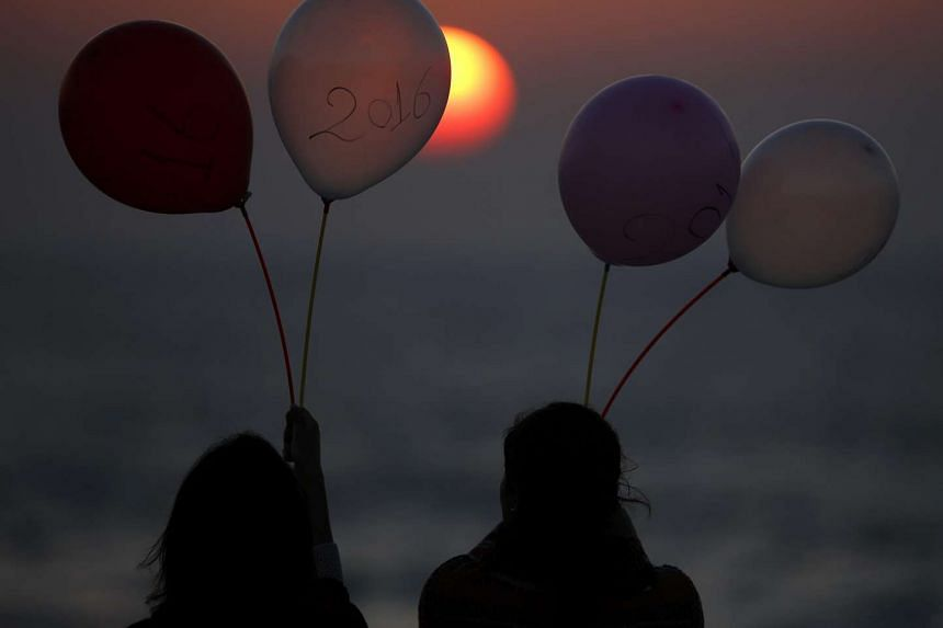 Two Palestinian girls watch the sunset holding balloons with 2016 written on one of them, in west Gaza City.