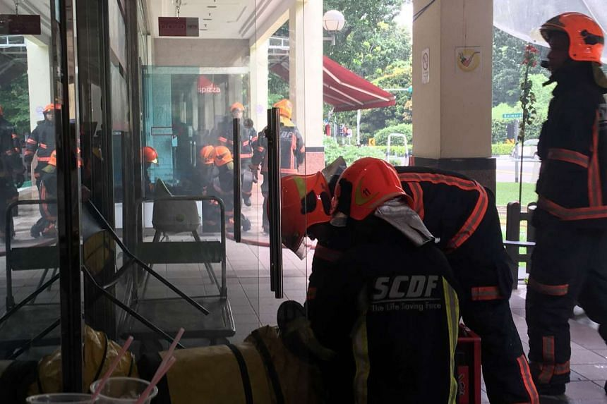 SCDF personnel outside the Italian eatery Spizza in Balmoral Plaza, where a fire broke out.
