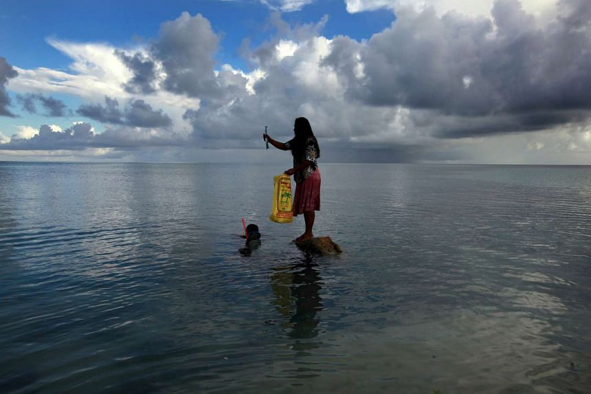A woman standing on top of a rock off Bikeman islet, Kiribati, in this May 25, 2013 file photo.