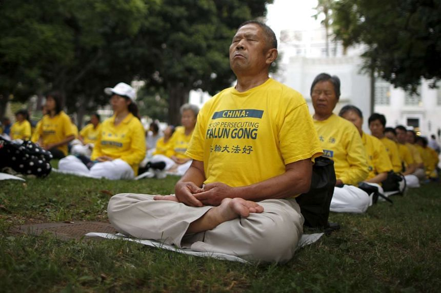 People practice Falun Dafa, or Falun Gong exercises before a protest march against the Chinese government  in Los Angeles on Oct 15 as Chinese President Xi Jinping arrived in Washington for a state visit.