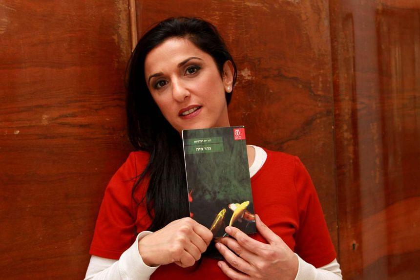 Israeli author Dorit Rabinyan poses with her Hebrew-language novel Gader Haya on Thursday at her house Tel Aviv.