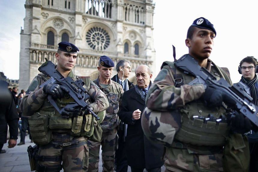 French Defence Minister Jean-Yves Le Drian (centre) talks with armed French soldiers on patrol in front of  theNotre Dame Cathedral in Paris on Wednesday.