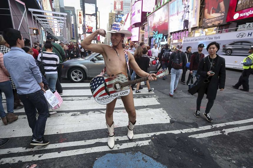 One of the Naked Cowboys poses in Times Square  the traditional site of tonight's New Year's Eve celebrations in Manhattan -  during unseasonably warm weather on Christmas Eve.