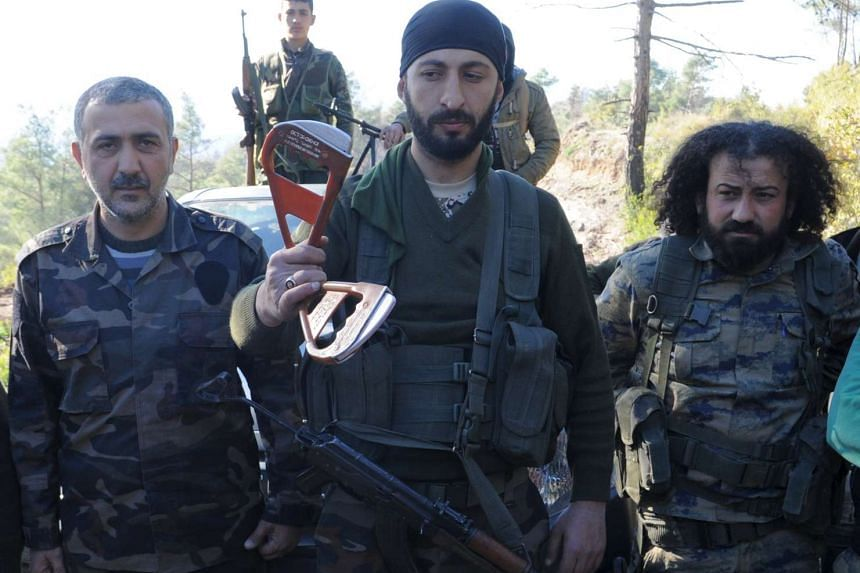 Alpaslan Celik (centre) holds handles believed to be parts of a parachute of the downed Russian warplane near the Turkish-Syrian border on Nov 24.