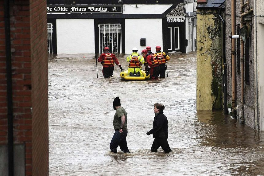 Residents wade through floodwater as members of the emergency services use a dinghy in Dumfries, Scotland on Dec 30, 2015.