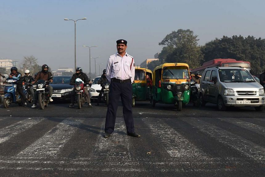 A traffic policeman stands at a traffic intersection in New Delhi on Dec 31, 2015.