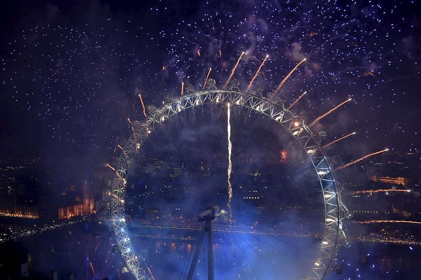 Fireworks exploding around the London Eye wheel, Big Ben clocktower and the Houses of Parliament to mark the beginning of the New Year in London, Britain, on Jan 1, 2016.